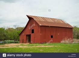 a red barn with a rusty tin roof on a farm in oklahoma stock photo