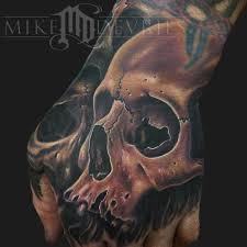 hand skull tattoo by mike devries tattoos