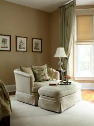 oversized master bedroom chair in front of a window partially covered by a shade and sage drape an