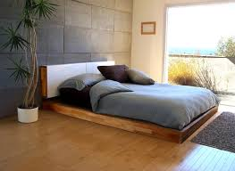 low bown teak bed frame with tiled white headboard under grey