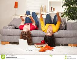 girls reading upside down on sofa stock images image 13326074
