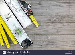 contractor work tools with floor plan on gray wooden background