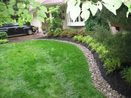 front yard bed lined with river stone and mulch to create a clean