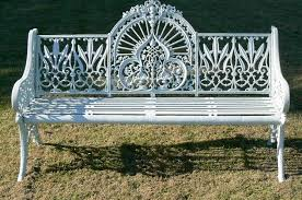 an antique coalbrookdale bench with ornate back and sides and an