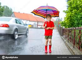 kid boy wearing red rain boots and walking with umbrella u2014 stock