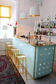 home bar decor with gold acrylic stools and pendant lighting and