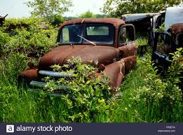 Vintage Ford Truck Junk Yards - old abandoned cars and pickup trucks in wrecking yard stock photo