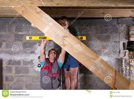 two men building stairs in unfinished basement stock photo image