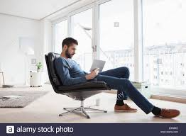 Sitting Chairs For Living Room Young Man Sitting On Leather Chair In His Living Room Using