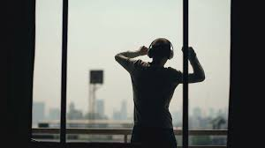 silhouette of young man dancing ad listening music in wireles
