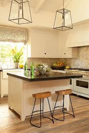 cream kitchen cabinets with black marble countertop transitional