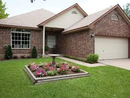 a raised flower bed with a cement bird bath adds curb appeal to