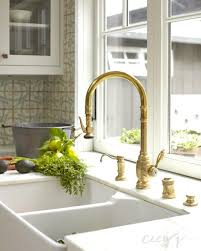 gold kitchen faucets lovely cottage kitchen features a white dual apron sink paired
