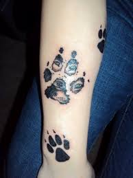 small black and white forearm tattoo of dog paw print stylized
