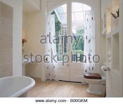 french doors with white voile curtains blowing in the wind stock