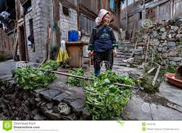 asian woman farmer miao people stands in courtyard peasant hous