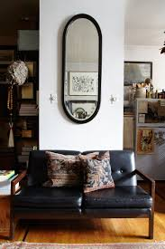 the studio apartment that breaks all the small space rules home a vintage loveseat gets a hit of texture from throw pillows fashioned out of antique rugs