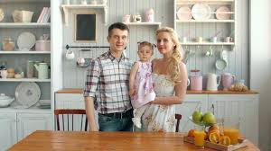 mother father and daughter cooking dinner in kitchen happy family