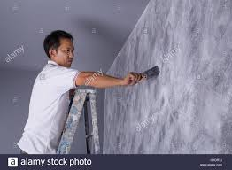 worker use brush for color paint concrete loft style on wall of