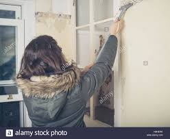 renovating a house a young woman wearing a warm winter coat is renovating a house and