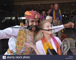 a rajasthani artist showing his long moustache to entertain