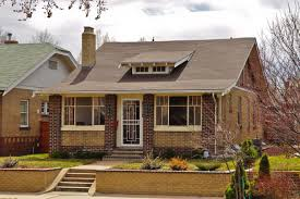 a standard bungalow styled house a low roof line and a glass door