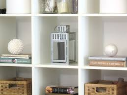 white wooden wall shelving unit with some racks and brown storages