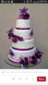 this white and purple wedding cake is topped off with a little