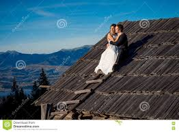 wedding couple sitting on the roof of country house honeymoon in