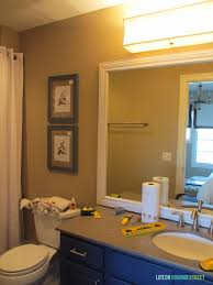 guest bathroom lighting and framing a builder grade mirror