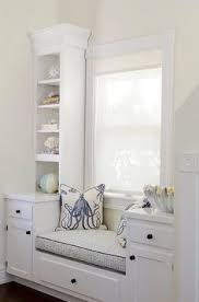a white built in window bench is placed in a recessed niche of a