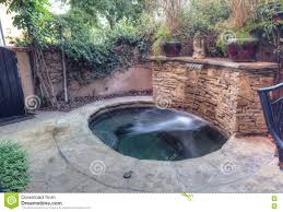 oval tub spa with waterfall and feng shui garden decor stock