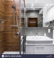 new style bathroom with wood effect tiles shower mirror and