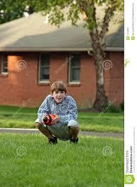 boy squatting holding football royalty free stock photo image