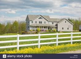 two story farmhouse style home and white fence in rural maine