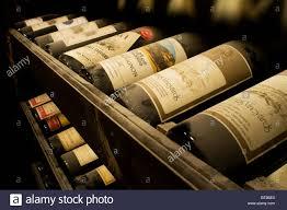 old vintage dusty wine bottles resting in wine cellar racks stock