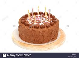 chocolate birthday cake with candles on wooden cutting board over