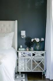 black and white bedroom with mirrored nightstand and gray greek