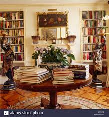 books in piles on circular antique table in library dining room