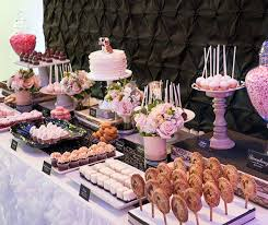 wedding dessert table displays a dessert table of lollipops cupcakes and jars of strawberry jelly