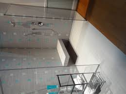 grey tiles shower areas wall with glass door on ceramics flooring