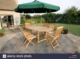 Teak Patio Umbrella by Teak Garden Table And Chairs On Patio With Large Umbrella Above