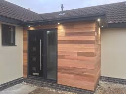 black door in timber clad porch they compliment each other