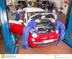 multiple auto mechanics repairing a car in garage royalty free