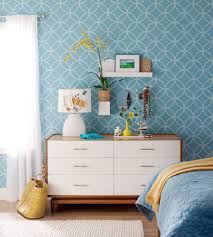 teal colored wallpaper with white wooden bedroom dresser design