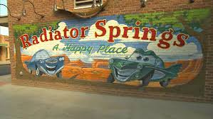 first look a drive through cars land transports disneyland guests radiator springs sign radiator springs mural