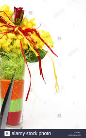red rose in a bouquet with yellow mimosa in glass vase