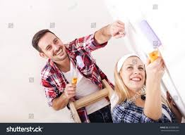painting a wall young couple painting wall roller doing stock photo 555928183