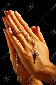 christian human praying with rosary in stock photo picture