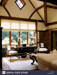 tudor style beams and high vaulted ceiling in country bedroom with stock photo tudor style beams and high vaulted ceiling in country bedroom with white blind on window above antique table